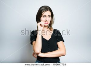 stock-photo-beautiful-girl-is-nervous-and-bites-nails-studio-photo-isolated-on-a-gray-background-459047728