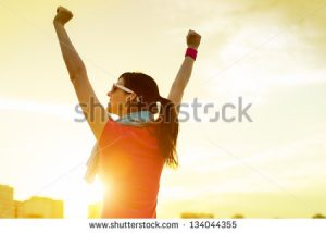 stock-photo-happy-successful-sportswoman-raising-arms-to-the-sky-on-golden-back-lighting-sunset-summer-fitness-134044355